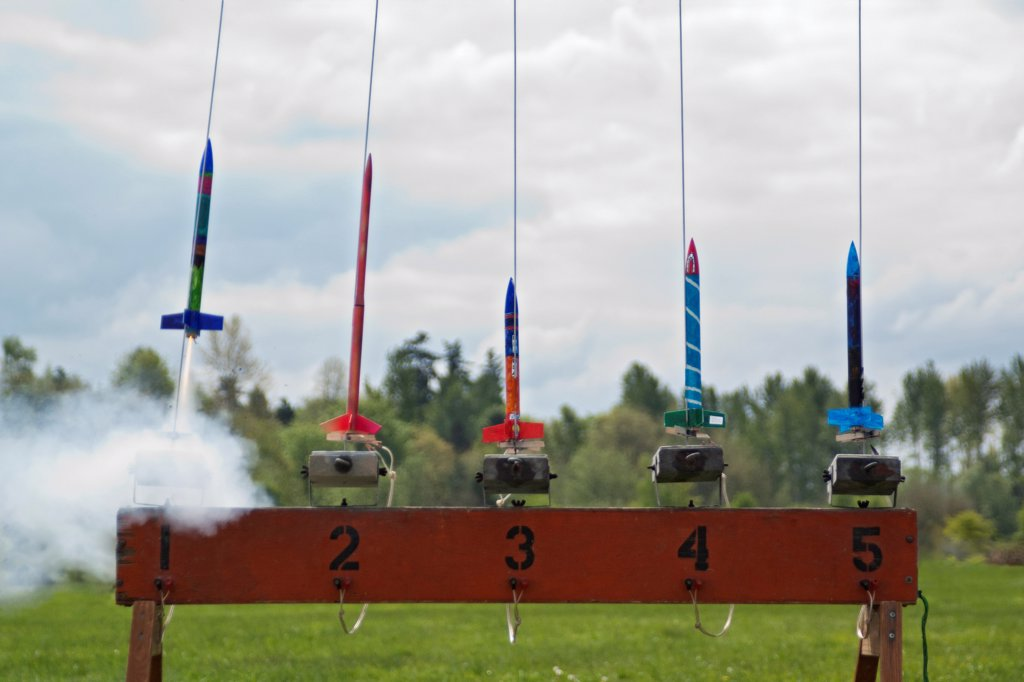 A row of brightly painted model rockets launch at a rocketry launch event. : Stock Photo