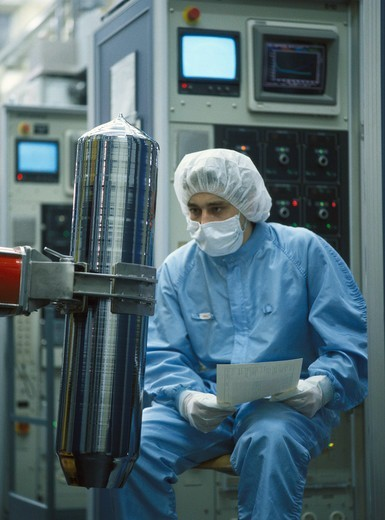 Stock Photo: 4359-644 Worker wearing protective clothing inspects a bar of silicon crystal