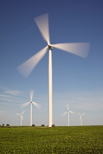 High Speed Green Energy Producing Wind Turbines Towering Above a Field of Crops : Stock Photo