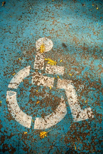 Handicapped parking space designated by icon of person in wheelchair : Stock Photo