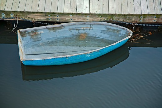 USA, Massachusetts, Gloucester, Blue rowboat without oars and half filled with rainwater at dock : Stock Photo