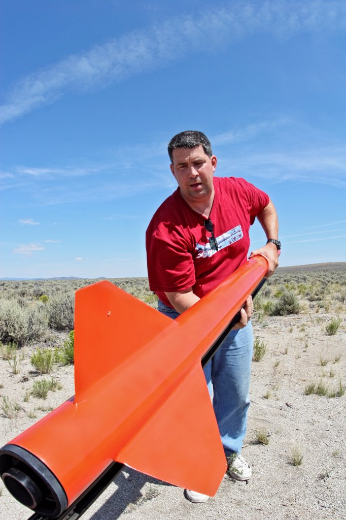 A man with the rear assembly of a red rocket (including fins and engine nozzle), at BALLS, an experimental rocketry event in the Black Rock Desert of northern Nevada. : Stock Photo