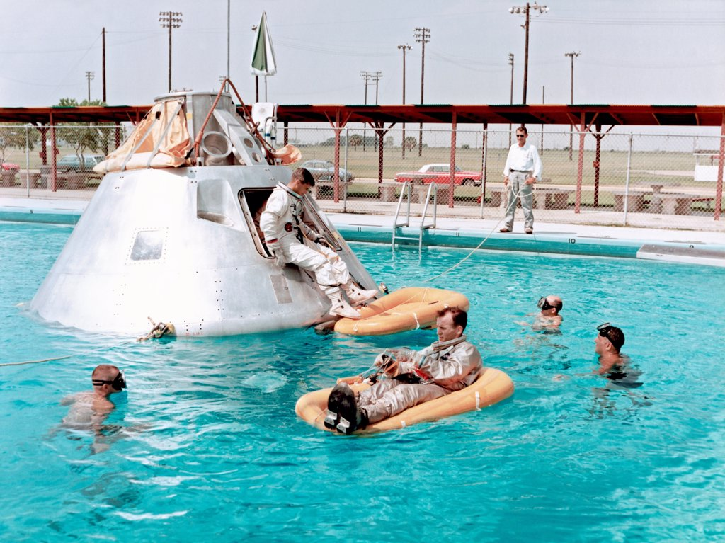 Stock Photo: 4368-170 Prime crew for the first manned Apollo mission practice water egress procedures with full scale boilerplate model of their spacecraft. Astronaut Edward H. White II rides life raft in the foreground. Astronaut Roger B. Chaffee sits in hatch of the boilerplate model of the spacecraft. Astronaut Virgil I. Grissom, third member of the crew, waits inside the spacecraft.
