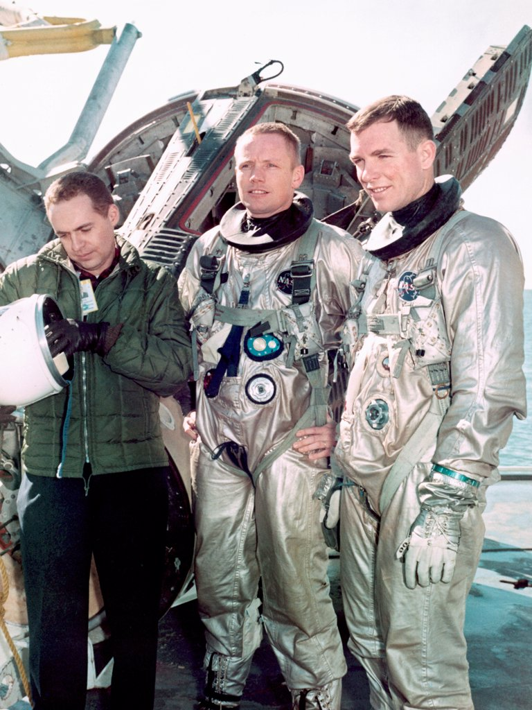 Stock Photo: 4368-171 Astronauts Neil A. Armstrong (center), command pilot, and David R. Scott (right), pilot of the Gemini 8 prime crew, are suited up for water egress training aboard the NASA Motor Vessel Retriever in the Gulf of Mexico. At left is Dr. Kenneth N. Beers, M.D., Flight Medicine Branch, Center Medical Office.