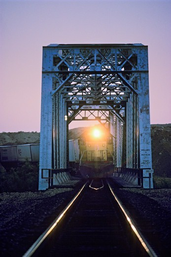 Stock Photo: 4369-528 Iron Railroad Bridge, Train, Headlight At Dusk