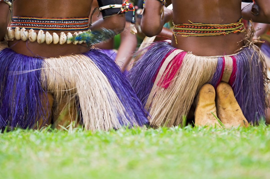 A rear view of children sitting on their feet during village visit and tour with dance performance by the children of Kitava Island, Trobriands, Papua New Guinea : Stock Photo