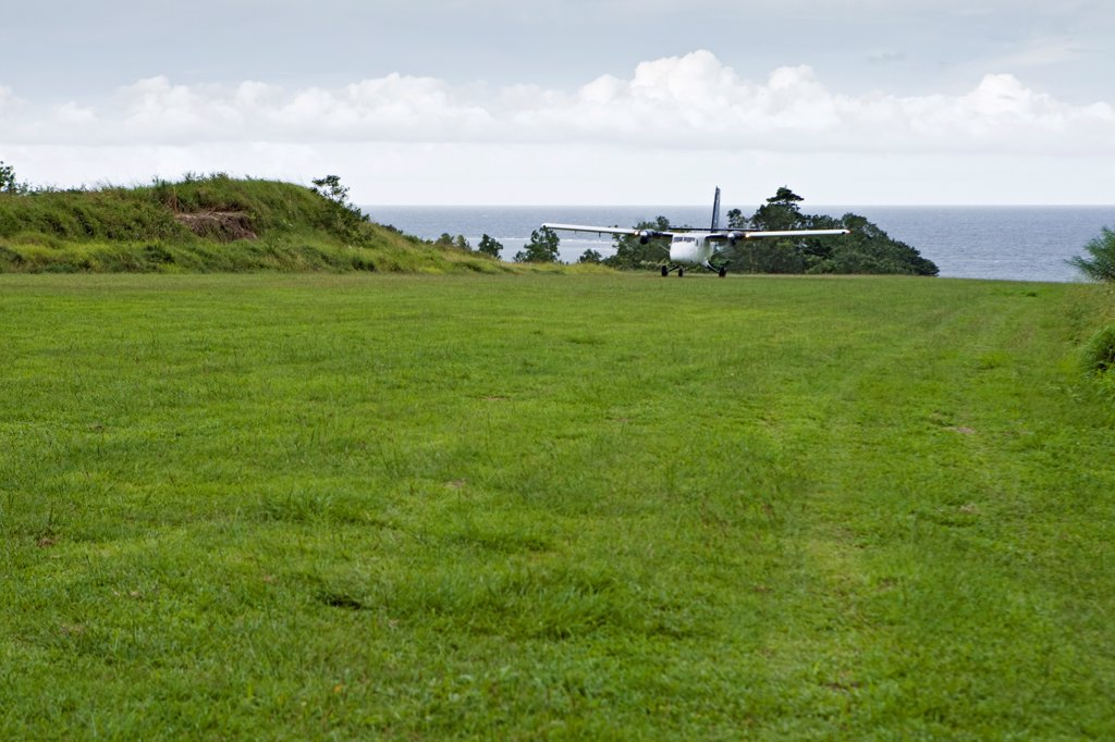 A plane lands on a grass landing strip of Oro Province, Papua New Guinea. : Stock Photo