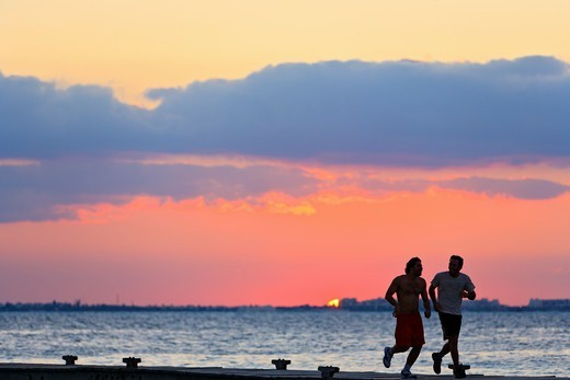 Jogging on the pier at sunset. : Stock Photo