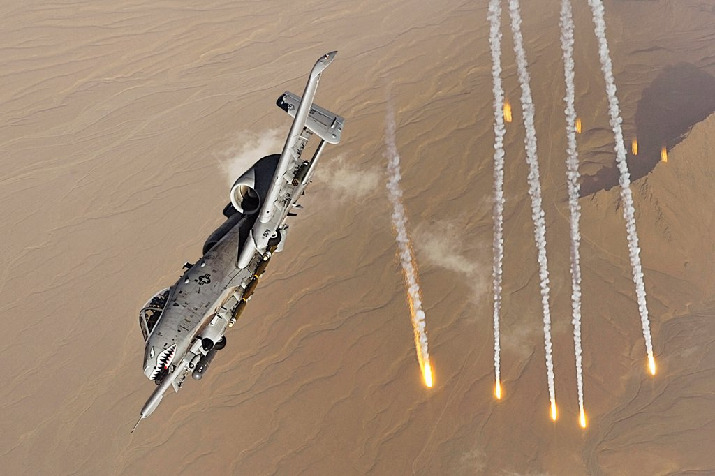 An A-10 Thunderbolt II deploys flairs over Afghanistan. A-10s provide close-air support to ground troops in Afghanistan and Iraq. The A-10's excellent maneuverability at low air speeds and altitude and its highly accurate weapons delivery make it an ideal aircraft for supporting coalition operations. (U.S. Air Force by photo by Staff Sgt. Aaron Allmon) : Stock Photo