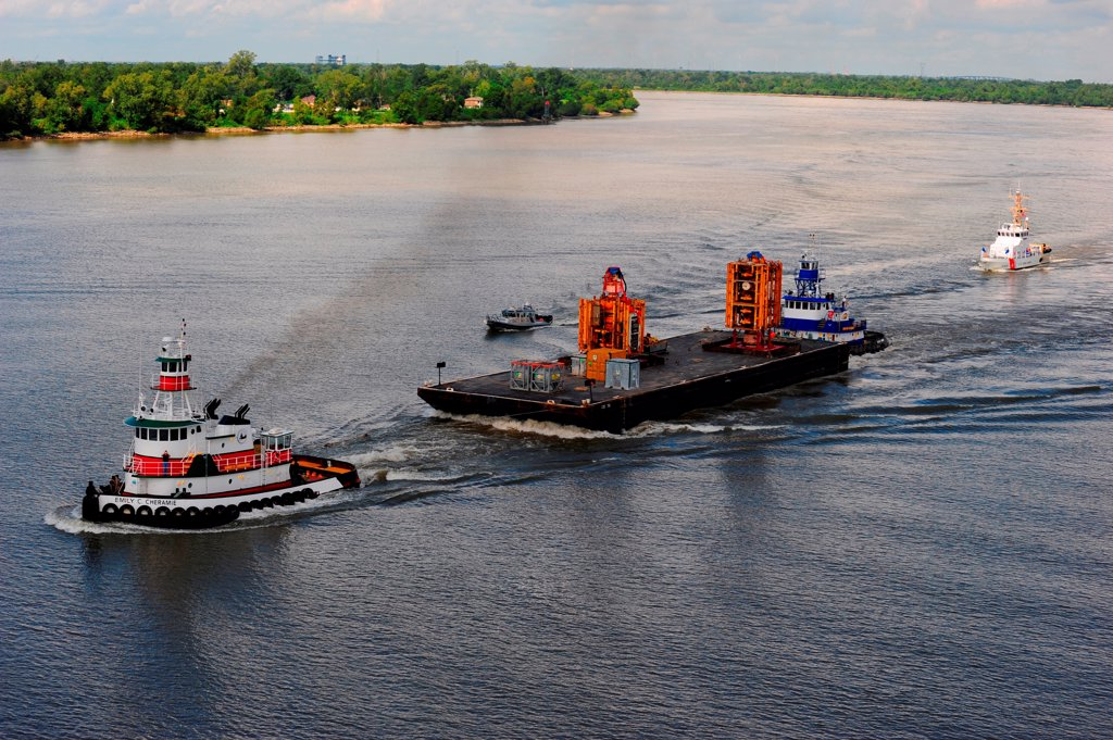 NEW ORLEANS -- Coast Guard, New Orleans Port Authority and Homeland Security units provide an escort as the blowout preventer of the Deepwater Horizon is transported on the Mississippi River into New Orleans, Sept. 11, 2010.  The blowout preventer will provide valuable insight into the cause of the oil discharge from the Deepwater Horizon. : Stock Photo