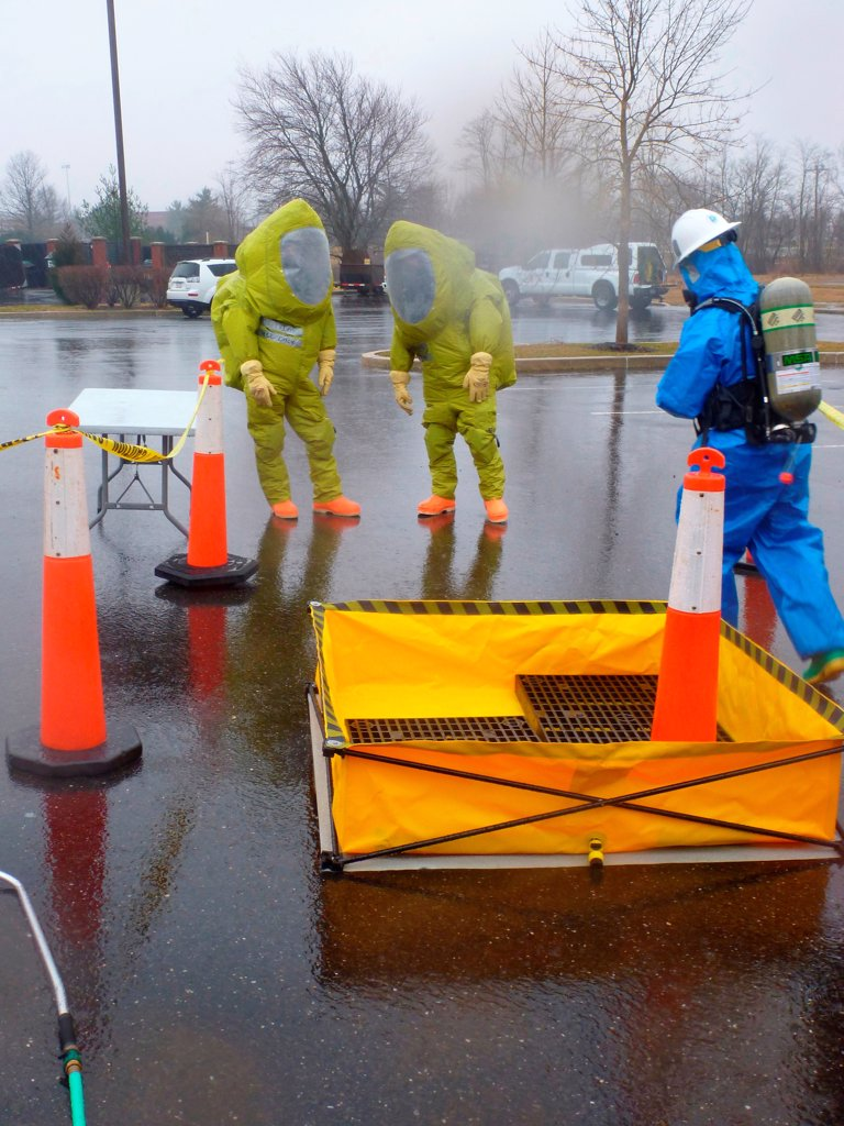 Stock Photo: 4385-335 FORT DIX, N.J. - Coast Guard Chief Broko Borland (right) of the Atlantic Strike Team prepares to decontaminate an entry team in protective clothing during a full-scale exercise at Joint Base Maguire-Dix-Lakehurst in Fort Dix, N.J., Feb. 29, 2012. The National Strike Force regularly conducts training to help improve readiness to hazardous material releases.
