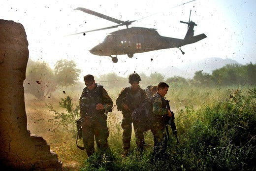 Afghan Commandos, with the Afghan National Army's 3rd Commando Kandak, shield their faces from flying debris after loading a wounded Commando on aUH-60 Blackhawk helicopter during a village clearing operation in Zhari district, July 6, 2011, Kandahar province, Afghanistan. : Stock Photo