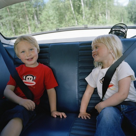 Two children in the back seat, Sweden. : Stock Photo