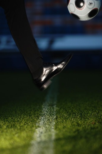 Stock Photo: 4400R-2515 A black shoe and a football.