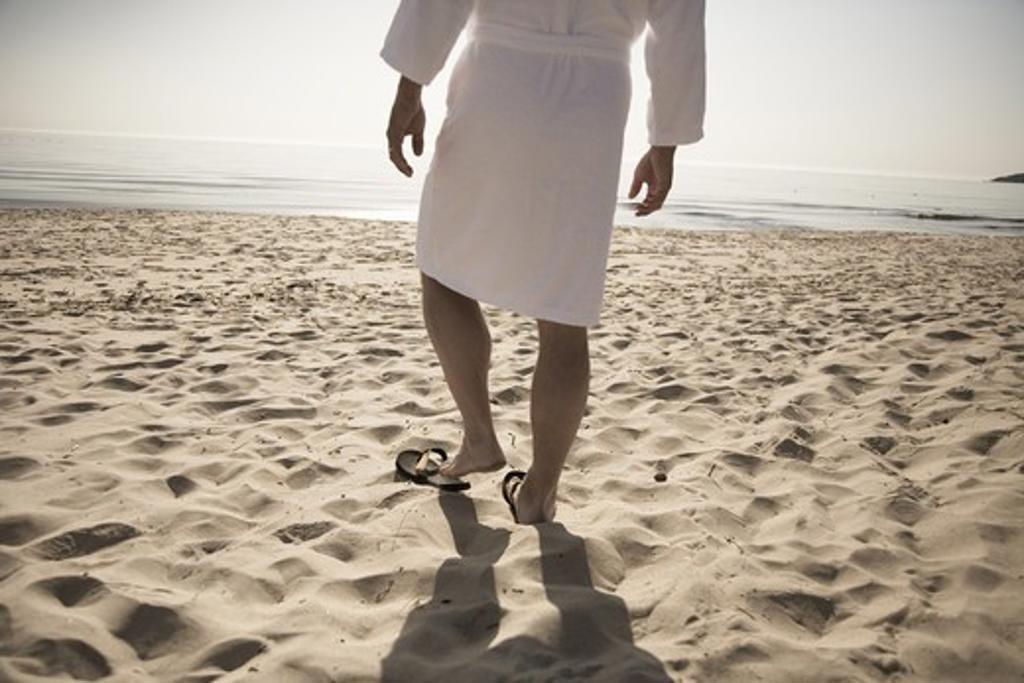 Man on a beach dressed in a bathrobe, Sweden. : Stock Photo