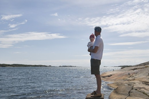 Father with children by the sea, Sweden. : Stock Photo