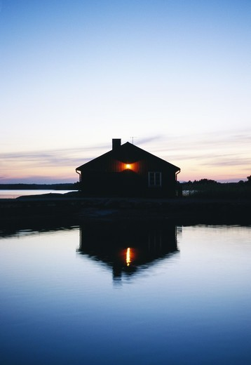 Boathouse reflected in the surface of water, Sweden. : Stock Photo
