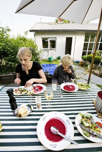 A women and a boy eating dinner outdoors : Stock Photo
