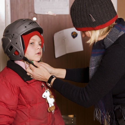 Mother helping child putting on a helmet, Sweden. : Stock Photo