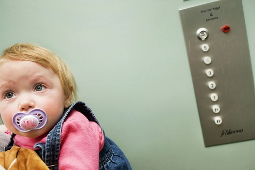 A sad baby girl in an elevator, Sweden. : Stock Photo