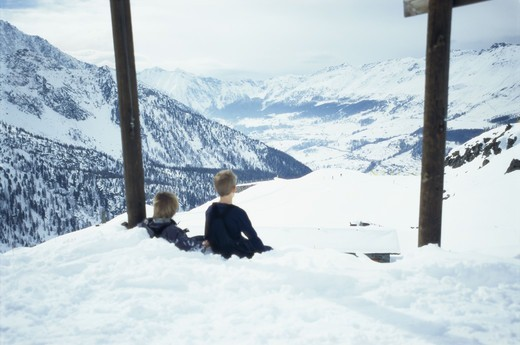 Two boys sitting in the snow up on a mountain, Italy. : Stock Photo