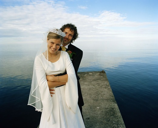 Stock Photo: 4400R-4096 Scandinavia, Sweden, Oland, Groom and bride embracing on jetty, smiling, portrait