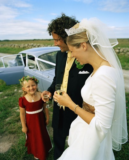 Scandinavia, Sweden, Oland, Bride and groom with flower girl, smiling : Stock Photo