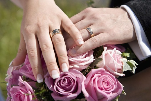 Stock Photo: 4400R-4292 Bride and groom with wedding rings on top of bouquet