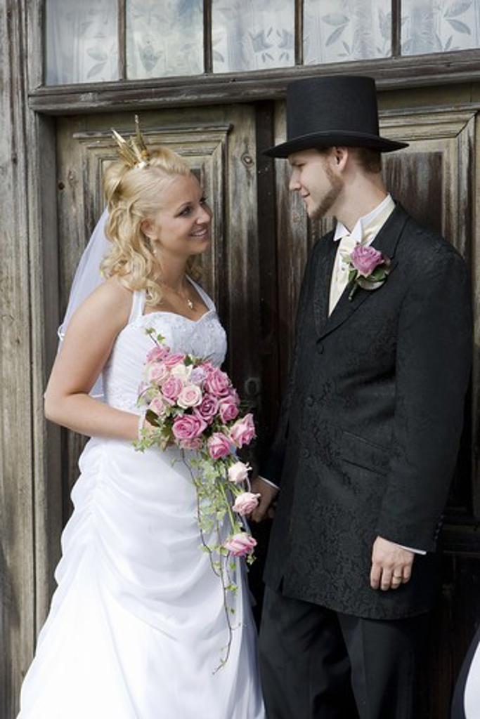 Stock Photo: 4400R-4295 Bride and groom standing in front of wooden door