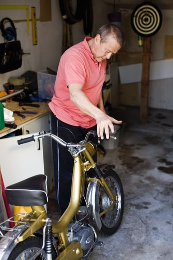 Stock Photo: 4400R-4499 Man repairing scooter