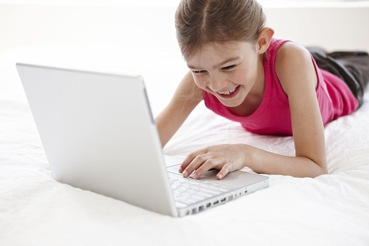 Stock Photo: 4400R-4688 Girl using laptop on bed, smiling