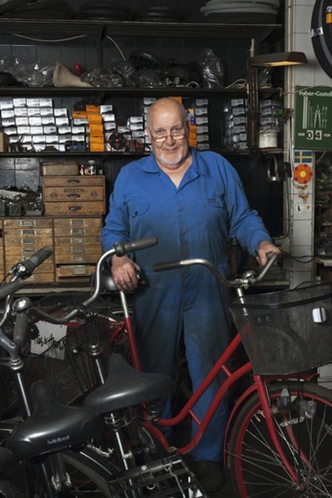 Stock Photo: 4400R-4782 Senior man standing in repair shop, smiling