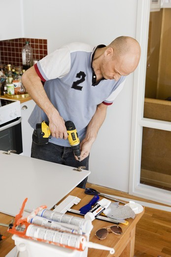 Stock Photo: 4400R-4790 Mid adult man using drill and repairing furniture