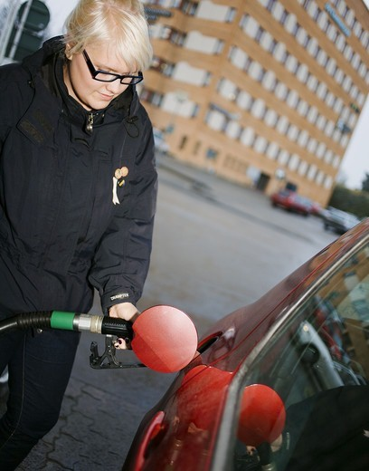 Stock Photo: 4400R-6026 A young Scandinavian woman filling up the tank of a car, Sweden.