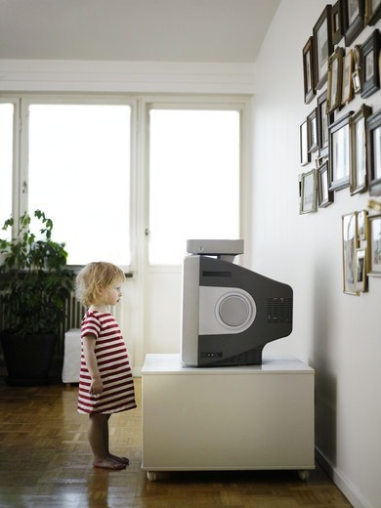 A little girl watching TV, Sweden. : Stock Photo