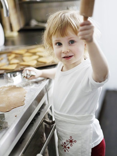 A little girl baking gingerbread, Sweden. : Stock Photo