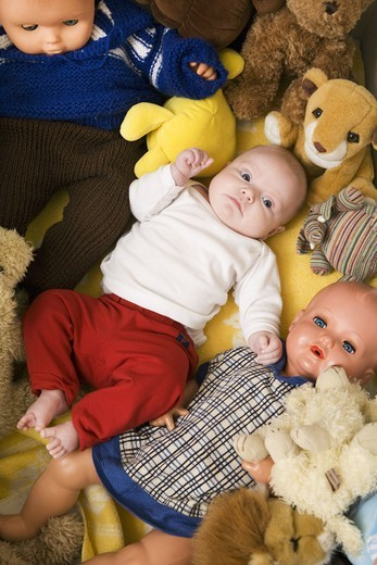 Stock Photo: 4400R-6212 A baby in a bed with cuddly toys and dolls, Sweden.