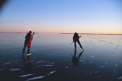 Stock Photo: 4401R-10208 Two people skating on a lake at sunset, Sweden.