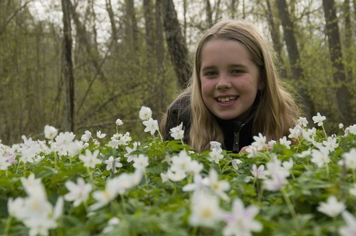 Scandinavia, Sweden, Smaland, Girl with white anemones in foreground, smiling, portrait : Stock Photo