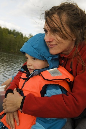 Mother and son with life jacket sitting on boat : Stock Photo