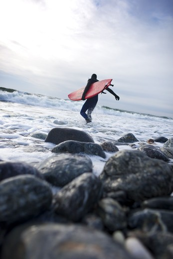 Stock Photo: 4401R-13800 Surfer carrying surfboard into sea