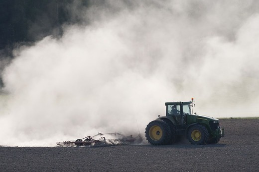 Tractor and dust on field : Stock Photo