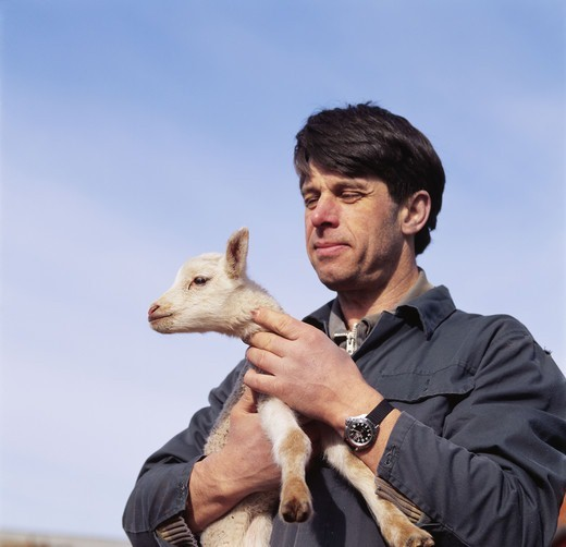 Stock Photo: 4401R-2033 Man holding lamb