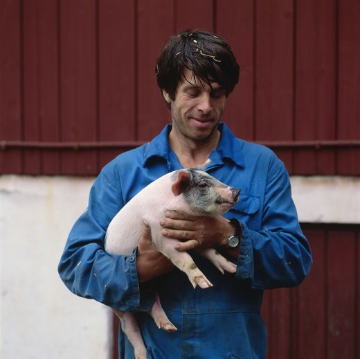 Stock Photo: 4401R-2038 Young man holding piglet