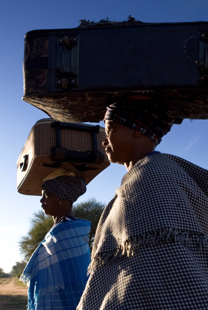 Ndebele women carrying suitcases balanced on their heads, South Africa : Stock Photo