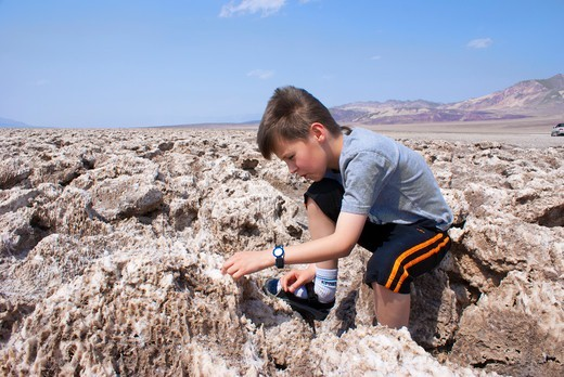 Stock Photo: 4404-1464 USA, California, Death Valley, Young geologist on Devil's Golfcourse