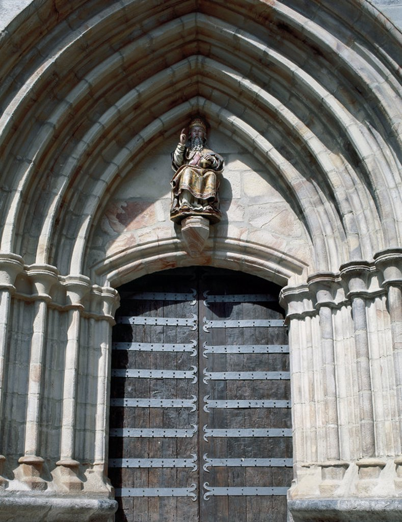 Gothic art. Spain. Church of St. John the Baptist. Door with archeries of pointed archs and seated sculpture of a saint in the tympanum. Mondragon. Province of Guipuzcoa. Basque Country. : Stock Photo