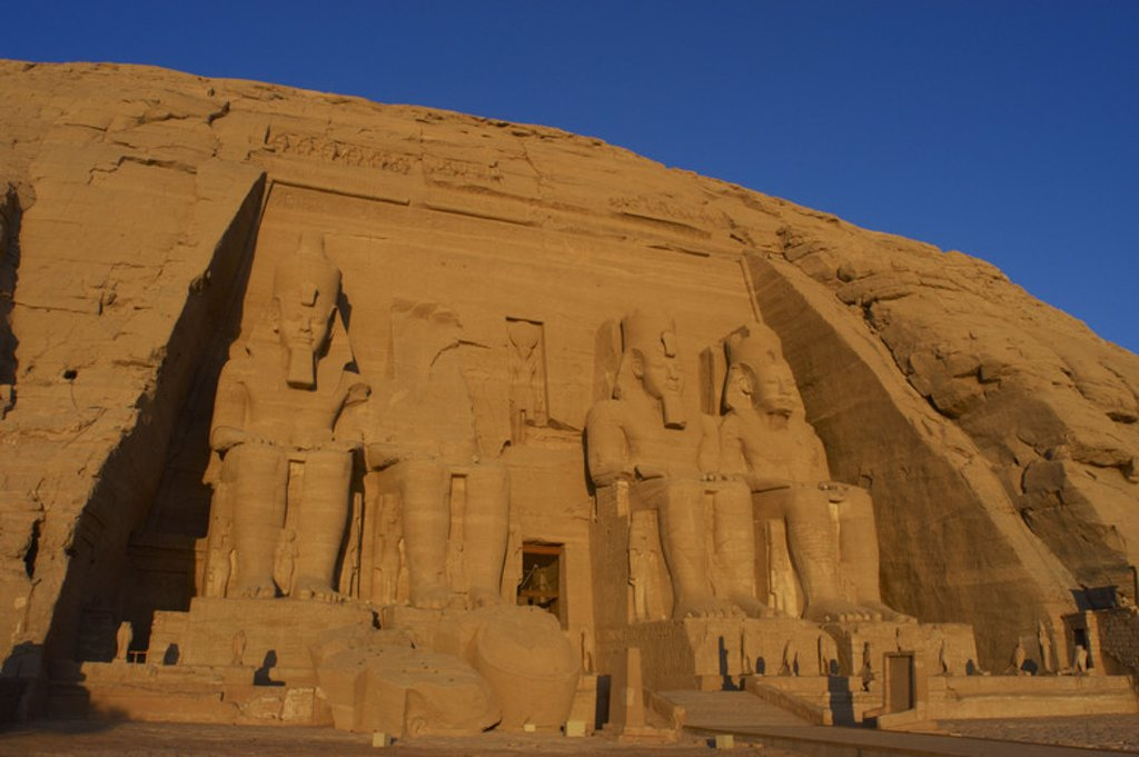 Egyptian art. Great Temple of Ramses II. Four colossal statues depicting the pharaoh Ramses II (1290-1224 BC) seated with the nemes head and surmounted by the double crown. 19th Dynasty. New Kingdom.  Abu Simbel. Egypt. : Stock Photo