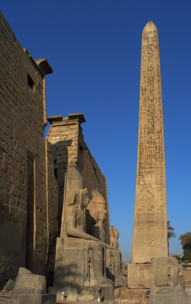 "EGYPT. TEMPLE OF LUXOR. Partial view of the first pylon of the temple, the remains of an obelisk of pink granite, and head and colossal statues of Ramses II. Ancient Thebes ""Waset,. : Stock Photo"