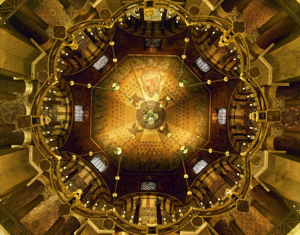Stock Photo: 4409-46845 Aachen Cathedral. Palatine Chapel. Low-angle shot of the bronze Barbarossa's Chandelier (1168) and the vault of the Octagon with golden mosaics depicting Christ surrounded by the 24 Ancients of the Apocalypse. By Salviati of Venice, 1882. Germany.